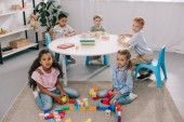 mnohonárodnostní předškoláky při hraní s dřevěných bloků v učebně při pohledu na fotoaparát