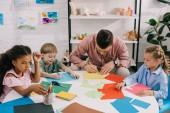 mnohonárodnostní předškoláky a učitel výrobu papíru nášivka v učebně u stolu