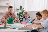 Fotografie učitel a mnohonárodnostní předškoláky řezání barevné papíry s nůžkami v učebně