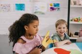 portrét multikulturní spolužáků sedí u stolu s doklady v učebně
