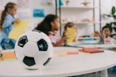 Photo selective focus of soccer ball on table and multiracial preschoolers in classroom