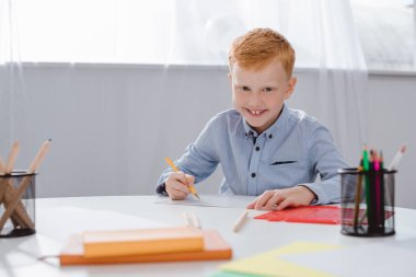 portrait of happy red hair preschooler boy sitting at table with paper and colorful pencils for drawing in classroom