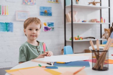 portrait of preschooler boy sitting at table with paper and colorful pencils for drawing in classroom