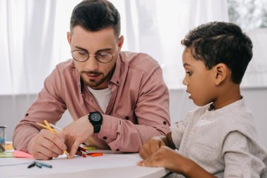 caucasian teacher and african american boy drawing picture together in classroom
