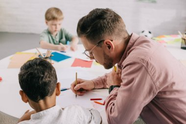 selective focus of teacher and multiracial boys drawing pictures with colorful pencils at table in classroom