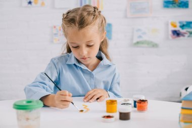 Portrait of adorable focused child drawing picture with paints and brush at table stock vector