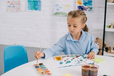 portrait of adorable focused child drawing colorful picture with paints and brush at table