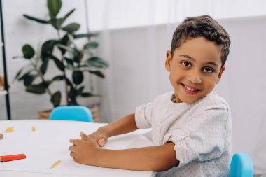 smiling african american boy with plasticine looking at camera at table in classroom