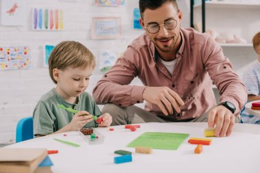 portrait of teacher and adorable preschooler with plasticine sculpturing figures at table in classroom