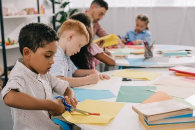 selective focus of teacher and interracial preschoolers cutting colorful papers with scissors in classroom