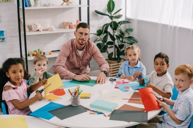 male teacher and multiracial preschoolers sitting at table with colorful papers in classroom