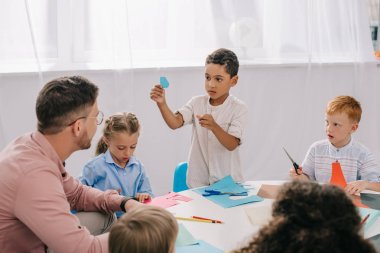 partial view of male teacher and multiracial preschoolers sitting at table with colorful papers in classroom