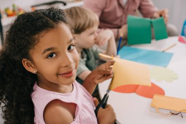 selective focus of multiethnic preschoolers cutting colorful papers with scissors in classroom