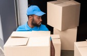 Photo high angle view of african american delivery man holding box near storage