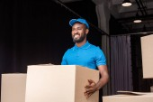 Photo smiling african american delivery man holding box near storage