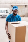 Photo african american delivery man carrying big box