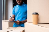 Fotografie african american delivery man writing something to clipboard with coffee to go on foreground