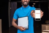 Oříznout obrázek africké americké doručovatel ukazující smartphone s aliexpress načtené stránky