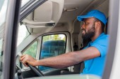 Fotografie side view of african american delivery man driving van