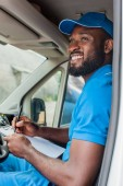 smiling african american delivery man holding clipboard and pen in van