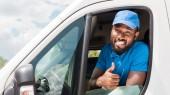 s úsměvem africké americké doručovatel ukazuje palcem od van