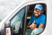 Fotografie smiling african american delivery man showing thumb up from car