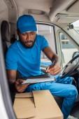 afro-amerikai szállítási ember tartja a vágólap és a toll van