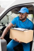 Fotografie african american delivery man going out from car with box
