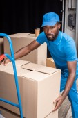 Fotografie african american delivery man putting boxes on cart