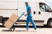 Fotografia side view of african american delivery man with cart and boxes