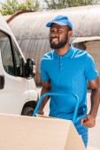 Photo african american delivery man with cart and boxes looking away