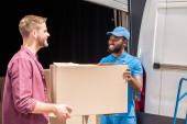 africká americká courier a kavkazské klient drží dodání box