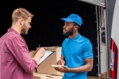 african american courier counting cost of delivery, client writing to clipboard