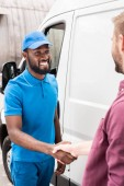 Photo multicultural courier and client shaking hands near van