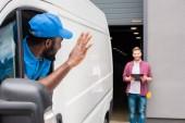 africká americká courier mává rukou klientovi