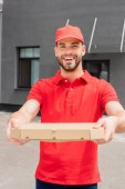 Photo smiling caucasian delivery man holding box with pizza and looking at camera