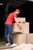 Fotografie young delivery man in red uniform with cardboard boxes