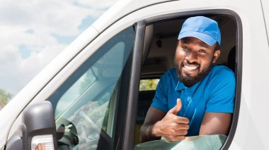 smiling african american delivery man showing thumb up from van