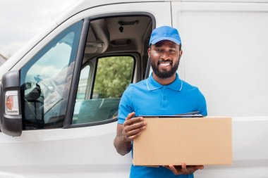 smiling african american delivery man holding cardboard box and looking at camera