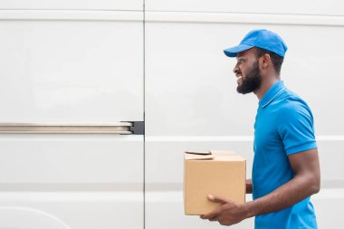side view of smiling african american delivery man carrying cardboard box