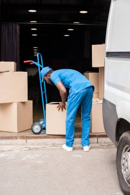 Side view of african american delivery man putting boxes on cart stock vector