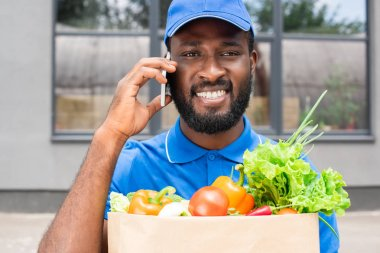 smiling african american delivery man holding paper bag with vegetables and talking by smartphone