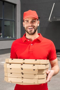 Smiling caucasian courier holding boxes with pizza stock vector