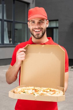 Smiling caucasian delivery man holding box with pizza stock vector