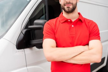 cropped shot of delivery man in red uniform with arms crossed standing at van