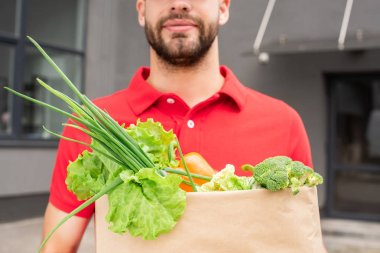 partial view of delivery man in red uniform holding paper bag with fresh vegetables