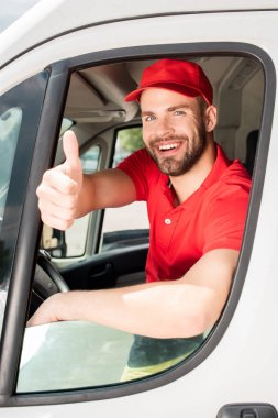 cheerful delivery man in white van showing thumb up
