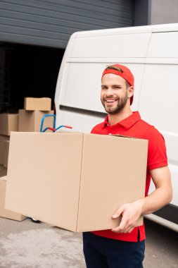 portrait of smiling delivery man in uniform holding cardboard box