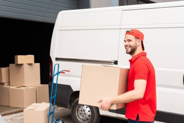 smiling delivery man in uniform with cardboard box standing near white van in street