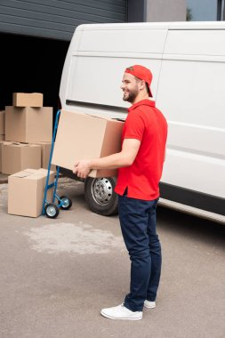 side view of young delivery man in uniform with cardboard box standing near white van in street